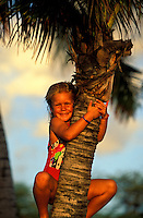 A little girl having fun climbing a palm tree at the beach on vacation on the Big Island