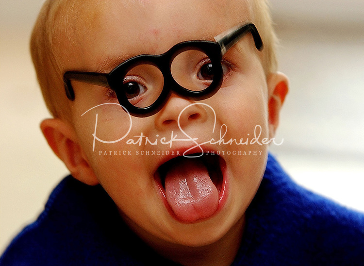A young boy goofs around by wearing Mr. Potato Head glasses.