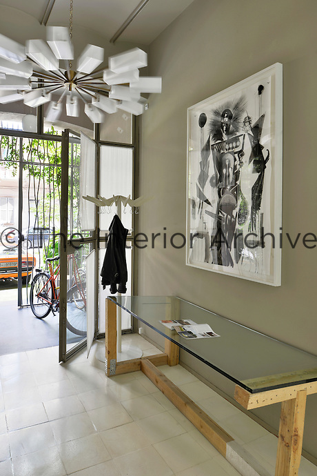 A light, modern entrance hallway with grey walls and a tiled floor. A monochrome artwork hangs above a functional wood table with a glass top.