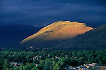 The sun spotlights Mount Jumbo on a July evening with dark clouds all around Missoula, Montana