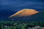 The sun spotlights Mount Jumbo on a July evening with dark clouds all around Missoula, Montana
