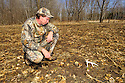 00273-043.14 White-tailed Deer Hunting:  Man is observing shed antler found in early spring in turnip food plot.
