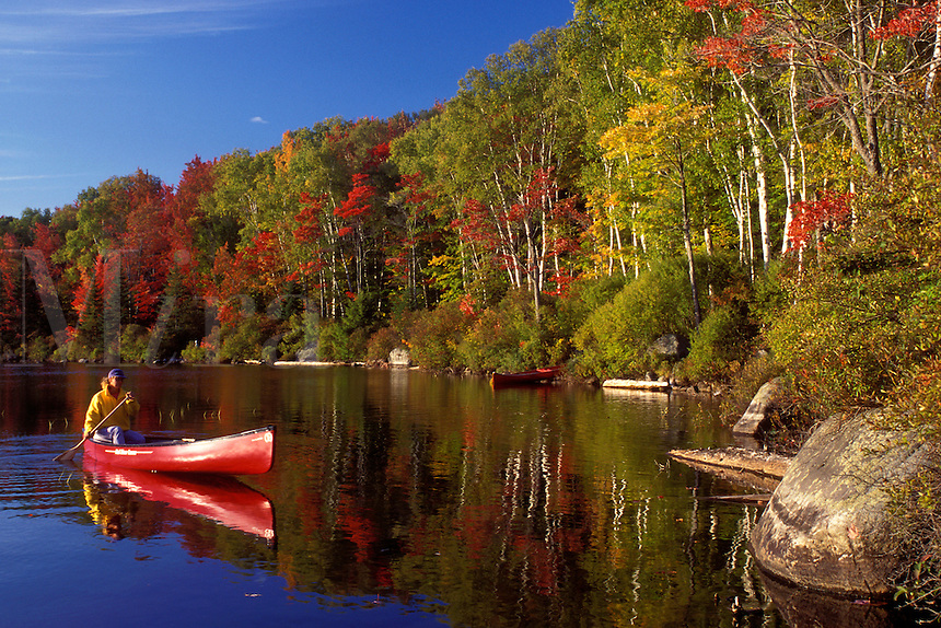 AJ1012, Vermont, canoe, canoeing, Woman paddling a red canoe on a sunny fall day on Kettle Pond in Groton State Forest. Mad River Canoe Products.