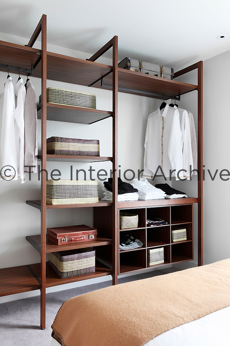 A wooden open shelving unit in the corner of a bedroom with wicker baskets for storage and neatly folded clothes and hanging shirts.