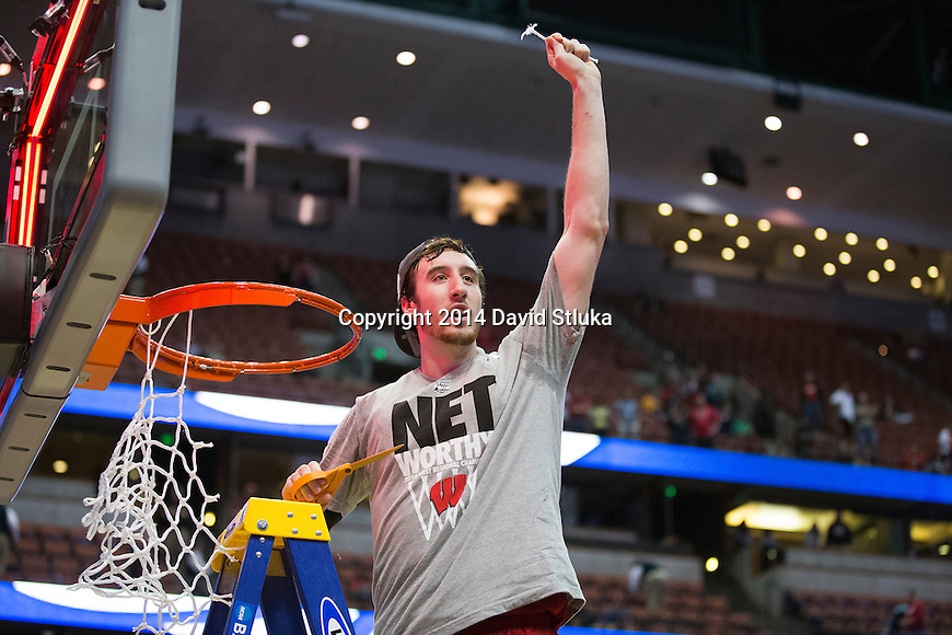 Wisconsin Badgers Frank Kaminsky cuts down a piece of the net after the Western Regional Final NCAA college basketball tournament game against the Arizona Wildcats Saturday, March 29, 2014 in Anaheim, California. The Badgers won 64-63 (OT). (Photo by David Stluka)