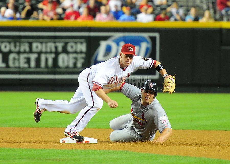 May 8, 2012; Phoenix, AZ, USA; Arizona Diamondbacks infielder Aaron Hill leaps over St. Louis Cardinals base runner Matt Holliday after turning a double play in the eighth inning at Chase Field. Mandatory Credit: Mark J. Rebilas-