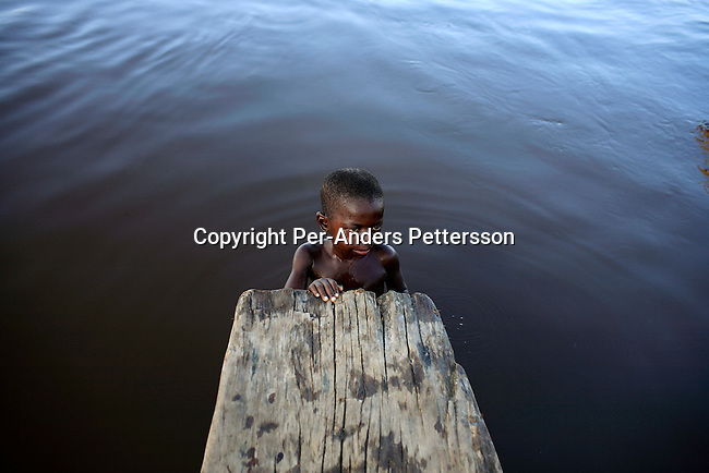 LUKUTU, DEMOCRATIC REPUBLIC OF CONGO MARCH 19: An unidentified boy takes a break while swimming on March 19, 2006 in the port in Lukutu, Congo, DRC. Lukutu, located along the Congo River, is a small village with a palm oil factory and an economy of agriculture and fishing. Congo River is a lifeline for millions of people, who depend on it for transport and trade. During the Mobuto era, big boats run by the state company ONATRA dominated the traffic on the river. These boats had cabins and restaurants etc. All the boats are now private and are mainly barges that transport goods. The crews sell tickets to passengers who travel in very bad conditions, mixing passengers with animals, goods and only about two toilets for five hundred passengers. The conditions on the boats often resemble conditions in a refugee camp. Congo is planning to hold general elections by July 2006, the first democratic elections in forty years..(Photo by Per-Anders Pettersson/Getty Images...
