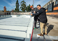 Tom Polansky, Associate VP of Facilities, and Greg Ochoa, Senior Project Manager, pour a bucket of water from Taylor Pool into the new pool of the De Mandel Aquatic Center at Occidental College, Dec. 12, 2019.<br /> (Photo by Marc Campos, Occidental College Photographer)