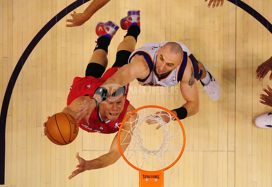 Mar. 2, 2012; Phoenix, AZ, USA; Los Angeles Clippers forward Blake Griffin (right) drives to the basket against Phoenix Suns center Channing Frye in the first half at the US Airways Center. The Suns defeated the Clippers 81-78. Mandatory Credit: Mark J. Rebilas-.
