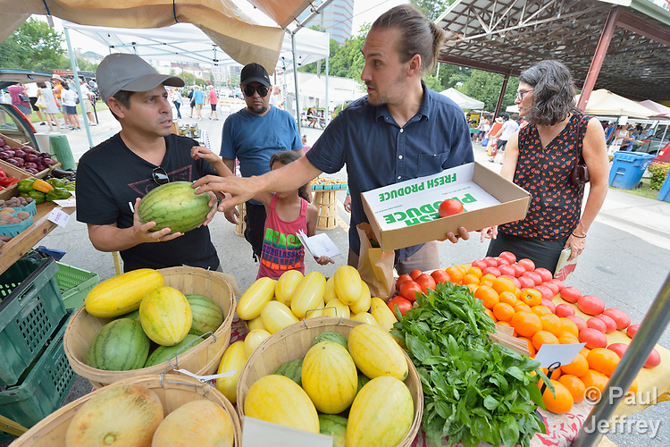Serguei Torres Miranda, a refugee from Cuba, discusses watermelons with a vender in the Durham Farmers' Market in Durham, North Carolina. The family was resettled in Durham by Church World Service, which resettles refugees in North Carolina and throughout the United States.<br /> <br /> Photo by Paul Jeffrey for Church World Service.
