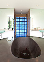 View over the circular stone bath towards the mirrored bathroom walls with matching glass basins