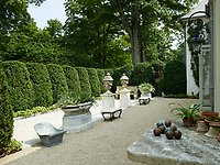The terrace is edged with topiary hedges and features limestone urns and planters.