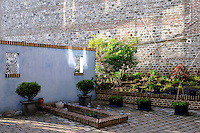 The courtyard garden is shielded on one side by a high flint and brick wall