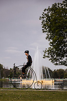 "A bicyclist atop a ""penny-farthing' or 'high wheel' bicycle passing the fountain in Denver's City Park."