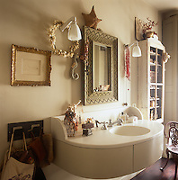 A mirror with a carved frame and two wall lights are placed above a washbasin in a unit. A wall mounted cupboard provides storage.