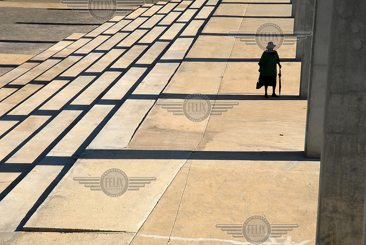 An elderly woman walks through Walter Sisulu Square in the area of Kliptown where the ANC's (African National Congress) Freedom Charter was signed...