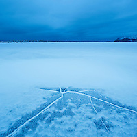 Crack in ice on frozen coastline at Ytterpollen, Lofoten Islands, Norway