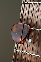 Pick (Plectrum) Under Strings on Guitar Fret Board