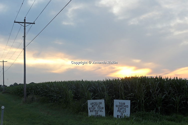 Signs in a cornfield on rural Illinois Route 71 protest the closing of the Arcelor Mittal plant in nearby Hennepin, Illinois in between Cedar Point and Granville, Illinois on July 20, 2009.  The plant, owned by the largest steel company in the world, Mittal, had previously employed 280 hourly workers and an unknown salaried employees.