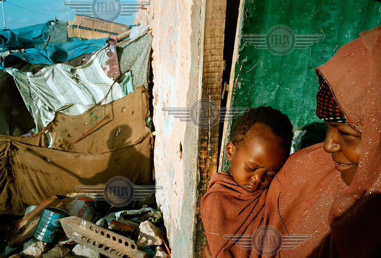 A Bantu woman and child stand outside their shelter.