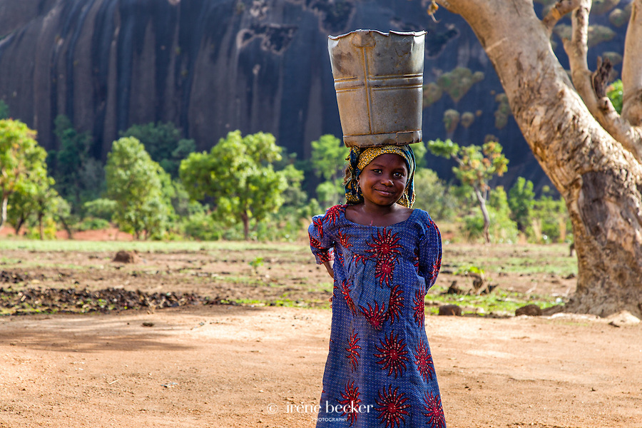 Fulani Girl carrying a bucket of water on her head in Kajuru, Kaduna State, Nigeria.