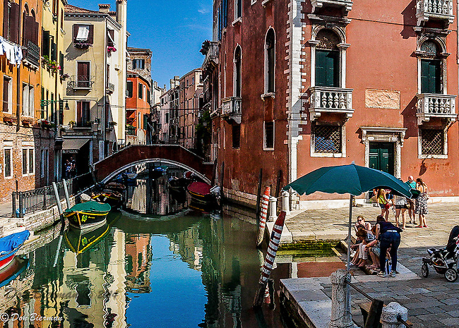 In Venice building reflections and colorful boars turn canals into artful vistas. Italy.