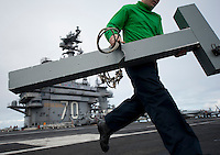 111206-N-DR144-926 PACIFIC OCEAN (Dec. 6, 2011) A Sailor assigned to Air Department's V-2 Division Visual Landing Aids shop runs to rig the Manually Operated Visual Landing Aids System (MOVLAS) during timed drills on the flight deck aboard Nimitz-class aircraft carrier USS Carl Vinson (CVN 70). Carl Vinson and Carrier Air Wing (CVW) 17 are currently underway on a Western Pacific deployment.  (U.S. Navy photo by Mass Communication Specialist 2nd Class James R. Evans/Released).