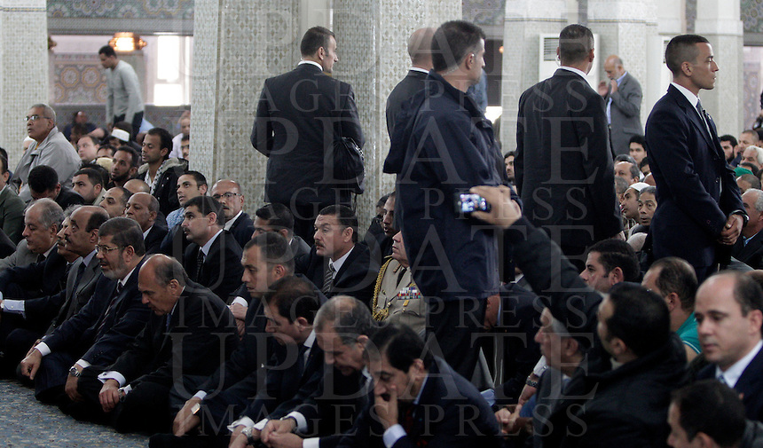 Il presidente egiziano Mohamed Morsi, in basso, quarto da sinistra, siede tra i fedeli radunati all'interno della Grande Moschea sotto lo sguardo delle guardie del corpo, a Roma, 14 settembre 2012..Egyptian President Mohamed Morsi, bottom, fourth from left, sits among faithful gathered inside the Great Mosque as bodyguards stand, in Rome, 14 September 2012..UPDATE IMAGES PRESS/Riccardo De Luca