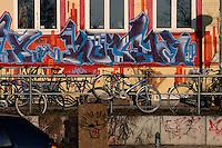 Bikes padlocked to metal bars next to grafitti covered walls, Hamburg, Germany.