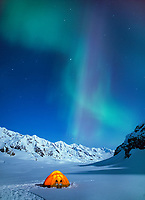 Yellow North face tent glows under a full moon night on the Canwell glacier in the Alaska Mountain range, the Aurora borealis swirls overhead.