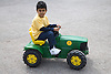 Young boy riding on a toy tractor,