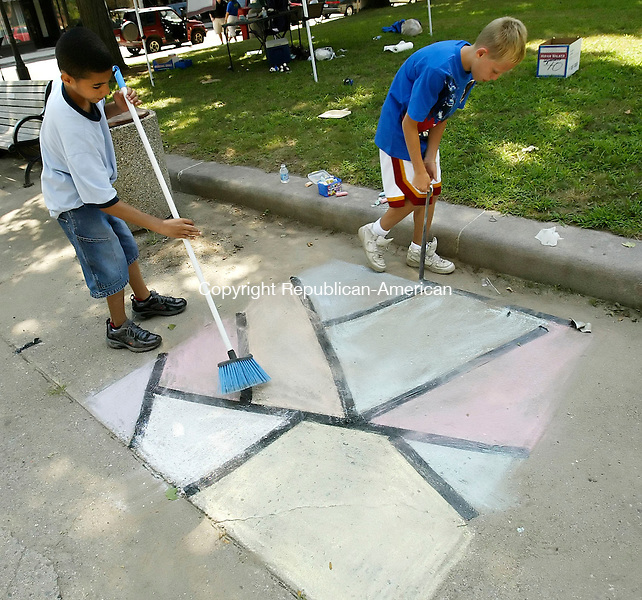 NAUGATUCK, CT, 04 August 2006, 080506BZ01- Kyle Johnson, 11, of Naugatuck, left, uses a broom to brush out chalk marks as his friend Alex Crean, 12, of Naugatuck, removes the border of their &quot;stained glass&quot; chalk creation during the 2nd annual Chalk The Walk event sponsored by the Naugatuck Arts Commission on the green in Naugatuck Saturday afternoon. <br /> Jamison C. Bazinet Republican-American