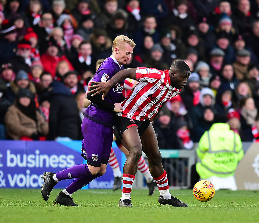 Lincoln City's John Akinde is fouled by  Grimsby Town's Ludvig Ohman<br /> <br /> Photographer Andrew Vaughan/CameraSport<br /> <br /> The EFL Sky Bet League Two - Lincoln City v Grimsby Town - Saturday 19 January 2019 - Sincil Bank - Lincoln<br /> <br /> World Copyright © 2019 CameraSport. All rights reserved. 43 Linden Ave. Countesthorpe. Leicester. England. LE8 5PG - Tel: +44 (0) 116 277 4147 - admin@camerasport.com - www.camerasport.com