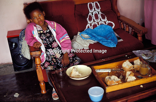 LSRURAL30094.Lifestyle. Rural. Eastern Cape. Young girl sitting on a couch with dry bread and a cup of tea on a tray before her. Low income family.  poverty.©Per-Anders Pettersson/iAfrika Photos