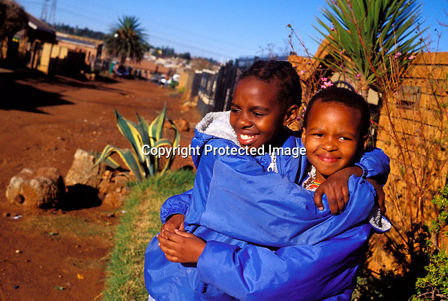 dippchi00229 Children SOWETO, SOUTH AFRICA - JULY 15: Unidentified girls playing in the street outside their home on July 15, 2002 in Soweto, a black township outside Johannesburg, South Africa. Soweto is the largest township in the country and itÕs estimated that about 3-4 million people resides there..©Per-Anders Pettersson/ iAfrika Photos..