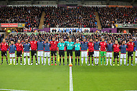 Match officials and team players huddle while the French National anthem is played before the Barclays Premier League match between Swansea City and Bournemouth at the Liberty Stadium, Swansea on November 21 2015