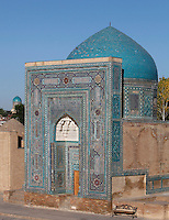 "General view of Mausoleum of the middle group, (""Nameless 1"" Mausoleum), 1380s, Shah-I Zindah ensemble, and in the distance the blue cupola of the Bibi-Khanym Madrasah and mausoleum, Samarkand, Uzbekistan, pictured on July 19, 2010, at dawn. The Shah-i-Zinda Complex is a necropolis of mausoleums whose legendary origin dates back to 676 when Kussam-ibn-Abbas arrived to convert the locals to Islam. So successful was he that he was assassinated whilst at prayer. His grave remains the centre of the sacred site which grew over many centuries, especially the 14th and 15th, into an architecturally stunning  exampleof ceramic art. The Mausoleum of the middle group.(""Nameless 1"" Mausoleum) was created by Usto Alim Nesefi, and is decorated with relief painted majolica. The portal decorations are notable for the symbol of ""octagonal stars"". Samarkand, a city on the Silk Road, founded as Afrosiab in the 7th century BC, is a meeting point for the world's cultures. Its most important development was in the Timurid period, 14th to 15th centuries. Picture by Manuel Cohen."