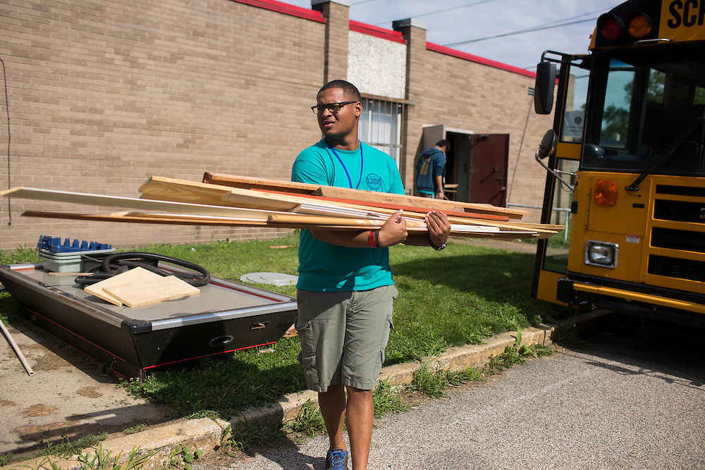 """Joshua Arrindell moves wood to a dumpster during """"Circle the City with Service,"""" the Kiwanis Circle K International's 2015 Large Scale Service Project, on Wednesday, June 24, 2015, at the Friendship Westside Center for Excellence in Indianapolis. (Photo by James Brosher)"""