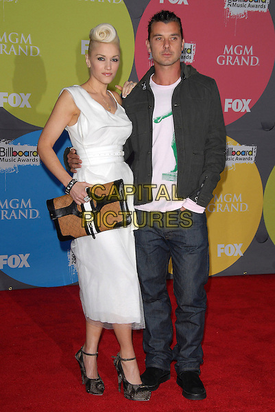 GWEN STEFANI & GAVIN ROSSDALE.Arrivals - 2006 Billboard Music Awards. held at The MGM Grand in Las Vegas, California, .USA, December 4th 2006..full length white dress hair quiff married husband wife couple waist belt brown bag grey platform ankle strap shoes.CAP/DVS.©Debbie VanStory/Capital Pictures