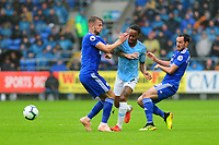 Raheem Sterling of Manchester City vies for possession with Joe Ralls (left) and Greg Cunningham (right) of Cardiff City during the Premier League match between Cardiff City and Manchester City at Cardiff City Stadium on  in Cardiff, Wales, UK. Saturday 22 September 2018