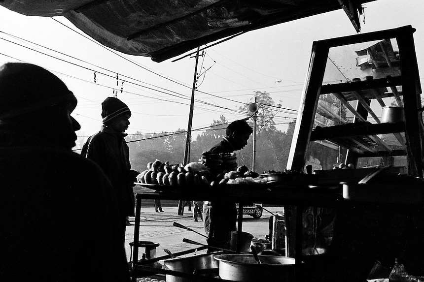 Young men wait in line at a food stall in Kathmandu, Nepal, 2008. Photo: Ed Giles.