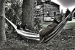 A cowboy relaxing in a hammock by an old log cabin