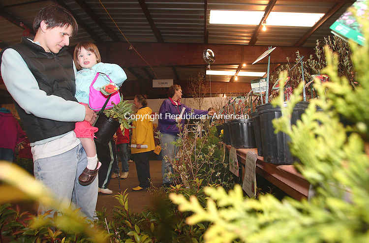 GOSHEN, CT-27 April 2007-042707MK03 Shannon Denver, from Barkhamstead, holds her three year old daughter Lily as they look over plants at the Northwest Conservation District's 25th annual Earth Day Plant sale at the Goshen Fair Grounds.  The event which runs today from 9 a.m. to 4 p.m. and tomorrow from 9 a.m. to 3 p.m. is a major fund raiser for the Conservation District.  Purchases provide funding for local conservation projects and education in addition to helping to curb climate change by planting items that absorb greenhouse gas pollution.   Michael Kabelka / Republican-American(Shannon Denver, from Barhamstead, holds her three year old daughter Lily ) CQ