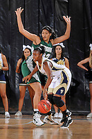 11 November 2011:  FIU's Kamika Idom (14) handles the ball while being defended by Jacksonville's Madison Scott (32) in the first half as the FIU Golden Panthers defeated the Jacksonville University Dolphins, 63-37, at the U.S. Century Bank Arena in Miami, Florida.