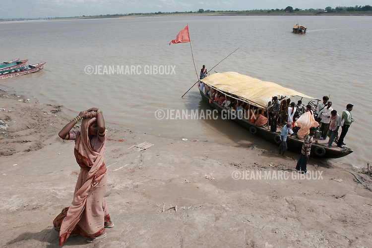 .VARANASSI, UTTAR PRADESH, INDIA - SEPTEMBER 12, 2005 : People use the ferry to cross the monsoon-swollen Gange river in Varanassi to reach Ramnagar and the Maharaja of Benares's Palace on the opposite side. Varanassi is one of the Holiest place in India, drawing millions of pilgrims every year. The Maharaja's Palace in Ramnagar is a witness to the ancient grandeur worth of a princely state, long lost since independance and democraty. (Photo by Jean-Marc Giboux)