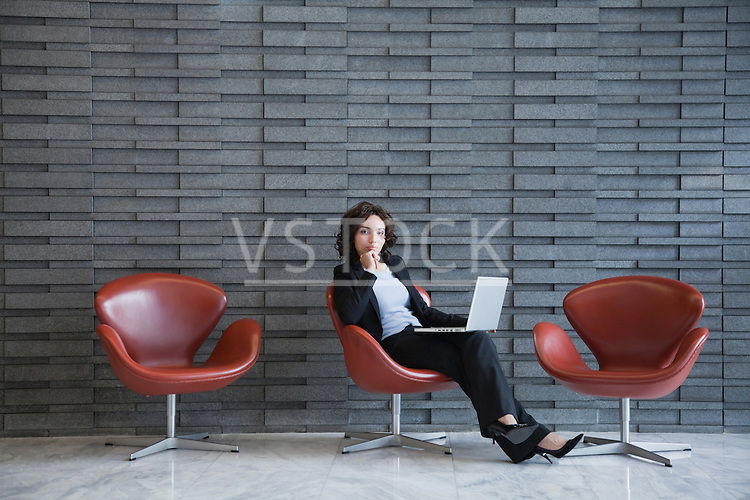 USA, New York, New York City, portrait of smiling young woman using laptop in hotel lobby