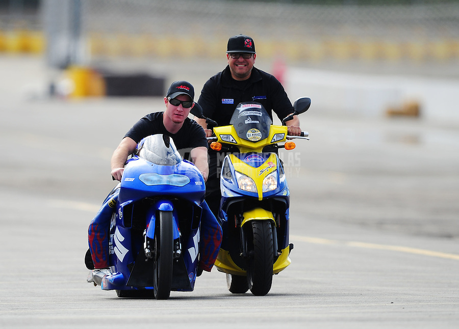 Nov. 11, 2011; Pomona, CA, USA; NHRA pro stock motorcycle rider Jim Underdahl (left) is pushed back to the pits by a crew member during qualifying at the Auto Club Finals at Auto Club Raceway at Pomona. Mandatory Credit: Mark J. Rebilas-.