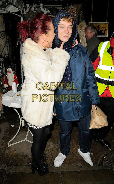 JAIME WINSTONE & ALFIE ALLEN .The Camden Passage Christmas Lights Switch On, Camden Passage, London, England, November 29th 2008..xmas switch-on Jamie full length cream fur coat leopard animal print mini dress ankle boots couple navy blue coat hood scarf headscarf brown paper bag  arm around shoulder finger smiling pointing  black tights jeans white trainers lace up ankle boots .CAP/CAN.©Can Nguyen/Capital Pictures