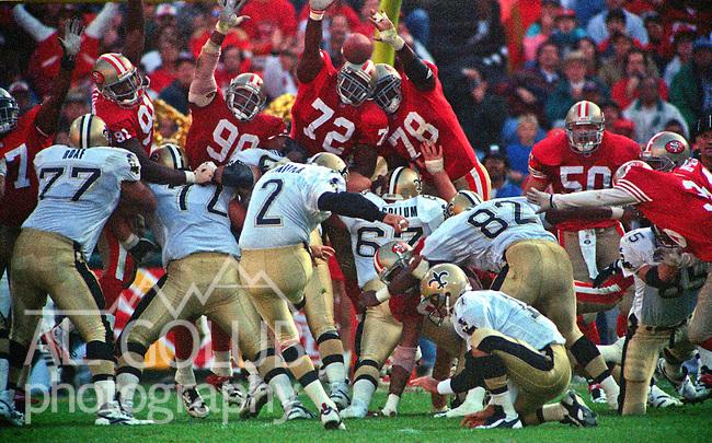 San Francisco 49ers vs. New Orleans Saints at Candlestick Park Sunday, October 29, 1995.  Saints beat 49ers  11-7.  San Francisco 49ers defensive end Oliver Barnett (72) and defensive end Michael Brandon (78) jump to block New Orleans Saints kicker Chip Lohmiller (2) kick with Klaus Wilmsmeyer (4) holding ball.