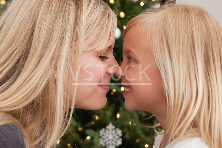 Mother and daughter (6-7) touching bonzes in front of Christmas tree
